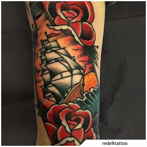 tatuaggio veliero rose e bottiglia